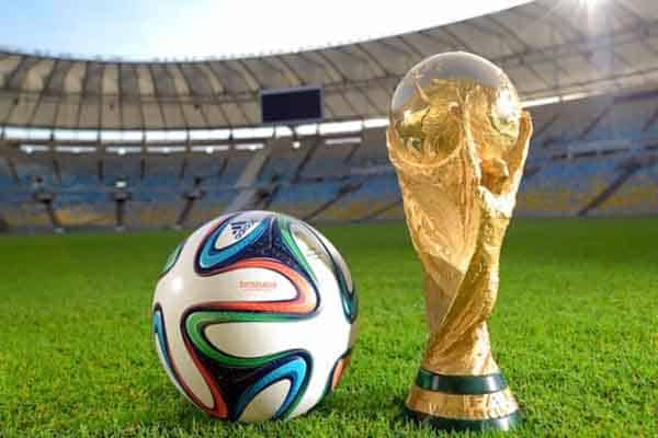 World cup trophy and soccer ball on field