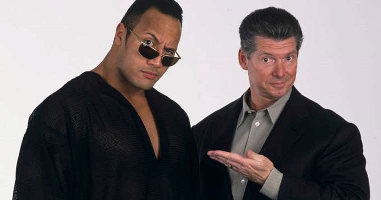 the Rock standing to the left of Vince McMahon