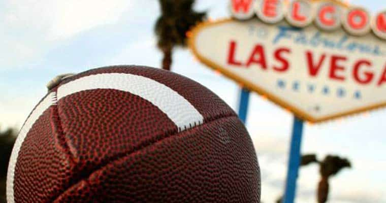 A football in front of the Los Vegas sign