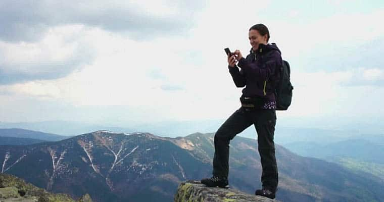 woman gambling on cell phone on a mountaintop