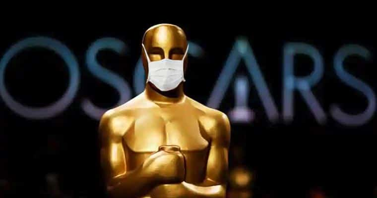 An Oscar Award statue with a surgical mask