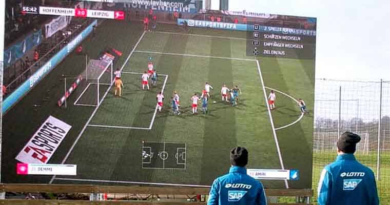 two people playing a soccer video game on a large screen